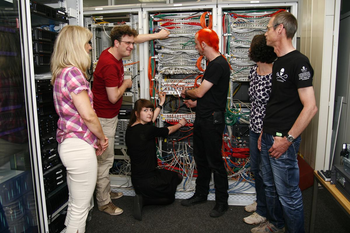 »Und da drin geht's zum Internet.« Heidrun Imo (in der Mitte kniend) zeigt der PERRY RHODAN-Redaktion im Serverraum das entscheidende Kabel. Foto: Peter Lehmann
